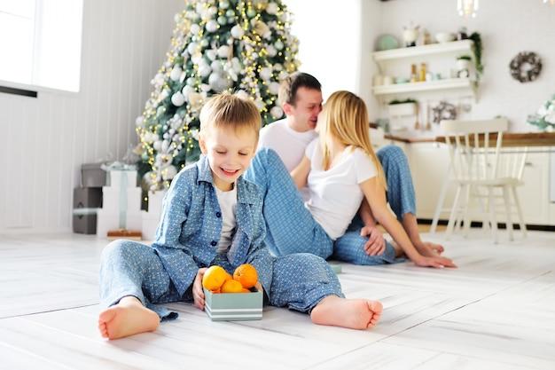 暖かい床に座っている青いパジャマを着た小さな子供男の子は、両親とクリスマスツリーの背景にみかんが入ったギフトボックスを開きます。クリスマスのお祝い。