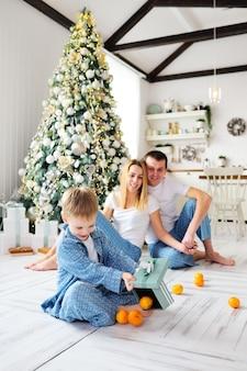 暖かい床に座っている青いパジャマを着た小さな子供男の子は、みかんの両親とクリスマスツリーのギフトボックスを開きます。クリスマスのお祝い。
