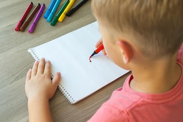 Маленький ребенок рисует домик маркерами на бумаге
