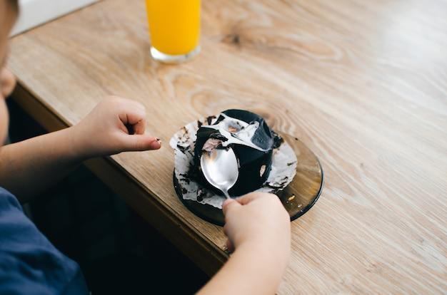 小さな子供が自宅のキッチンでブラックチョコレートケーキを食べる