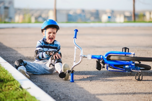 어린 아이가 자전거에서 도로로 떨어져 울면서 고통스럽게 비명을 질렀습니다.
