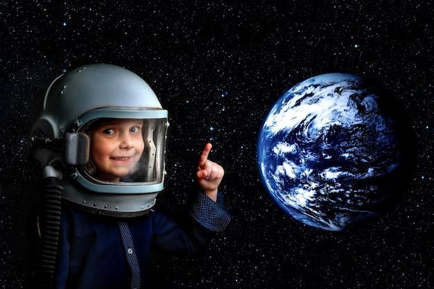Маленький ребенок воображает себя космонавтом в шлеме космонавта. элементы этого изображения предоставлены наса