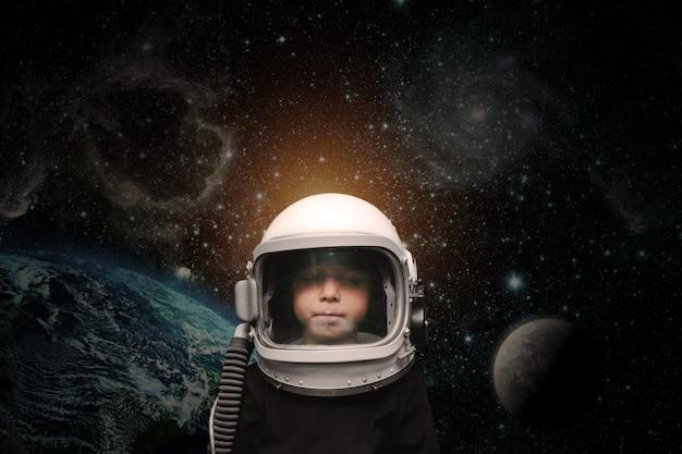 Маленький ребенок воображает себя космонавтом в шлеме космонавта.