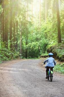 ヘルメットをかぶった小さな子供が、森の小道で二輪自転車に乗ることを学びます。親子の合同時間、アクティブなレクリエーション。