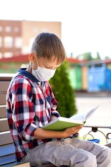 Маленький ребенок в маске со школьной сумкой во время вспышки вируса ходит в школу или детский сад.