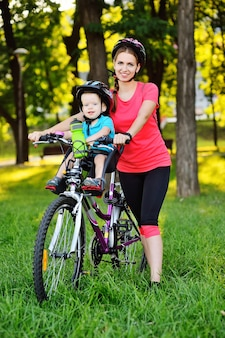 Маленький ребенок в защитном шлеме улыбается, сидя на детском велосипедном сиденье на большом горном велосипеде с мамой на поверхности зеленой травы и природы