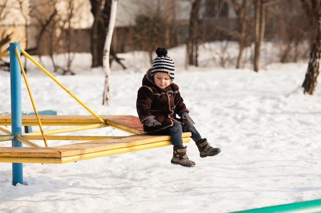 Маленький ребенок в теплой коричневой куртке и шляпе играет на детской площадке в зимний день