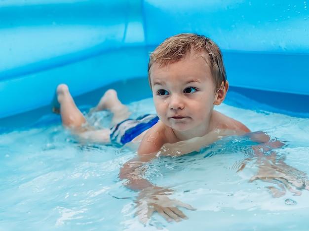 화창한 여름 날씨에 풍선 어린이 둥근 수영장에 있는 작은 아이. 여름과 휴가 개념입니다.