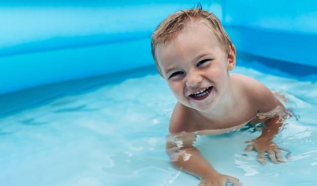 晴れた夏の天候のインフレータブルキッズラウンドプールの小さな子供。夏と休暇のコンセプト。