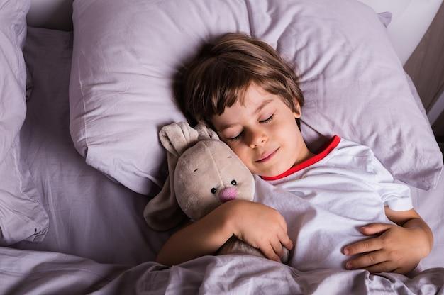 パジャマ姿の小さな子供がぬいぐるみのベッドの上の綿の寝具で寝ています