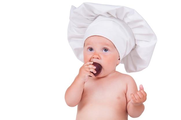 Маленький ребенок ест сливы в костюме повара на белом.