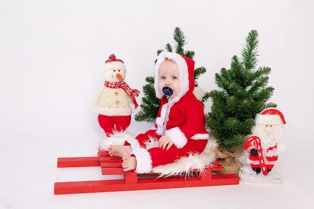 小さな子供がサンタのバスケットに座っている白い孤立した背景の帽子とクリスマスツリー、テキストのための場所