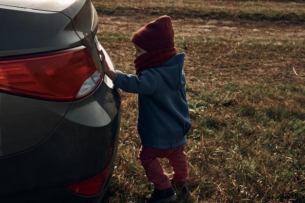 Маленький ребенок смотрит в открытое окно машины. маяк на заднем плане. путешествие с детьми.