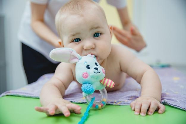 胃に横たわっている小さな子供が、おもちゃを口にしたマッサージルームでマッサージを受けます