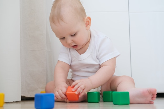 Маленький ребенок играет на полу с разноцветными кубиками и строит из них пирамиду.