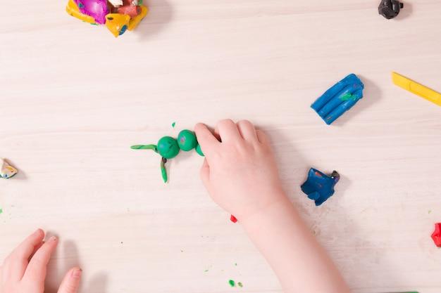 작은 아이가 나무 테이블에 녹색 플라스틱으로 애벌레를 조각합니다.
