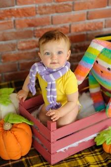 小さな子供が木箱に座っています。