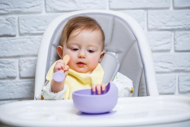 小さな子供がハイチェアに座って、スプーンで皿から食べ物を食べます。赤ちゃんを養うための赤ちゃん用シリコーン器具