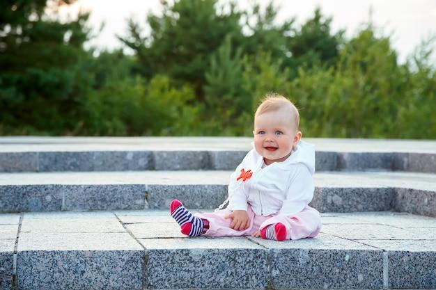 어린 아이가 바닥에 앉아 웃습니다.