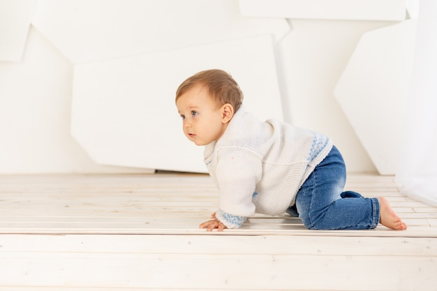 Маленький ребенок шести месяцев в вязаной теплой куртке и синих джинсах ползет дома по светлой комнате