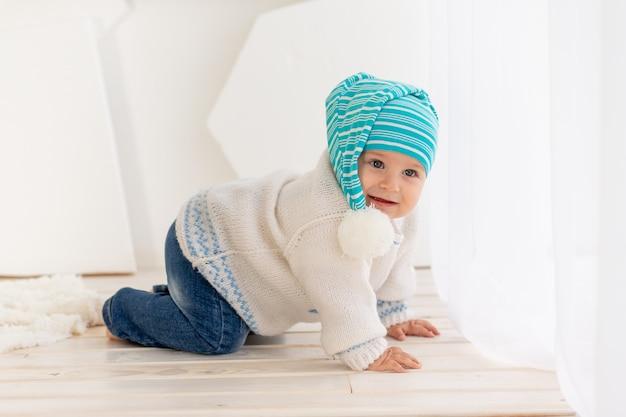 暖かいジャケットと帽子を編んだ生後6か月の小さな子供が、明るい部屋で家を這っています。