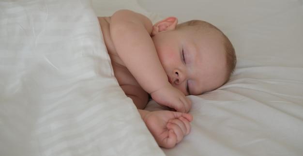 Маленький ребенок спит под белым одеялом.