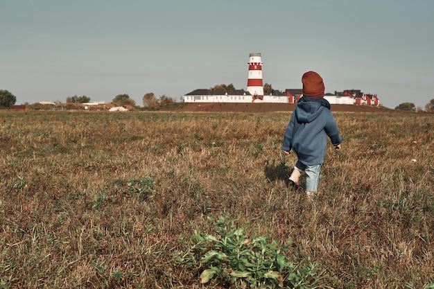 Маленький ребенок идет по полю на фоне маяка, ребенку два года. осенние прогулки на природе.