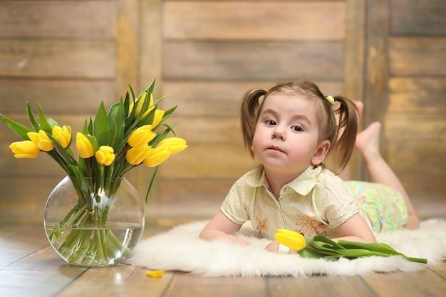 노란 튤립 꽃다발을 든 작은 아이. 꽃병에 꽃 선물을 든 소년. 바닥에 노란 튤립과 함께 여성 휴가에 여자를 위한 선물.