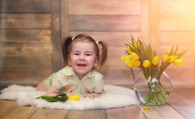 Маленький ребенок с букетом желтых тюльпанов. мальчик с подарком цветы в вазе. подарок девушкам на женский праздник с желтыми тюльпанами на полу.