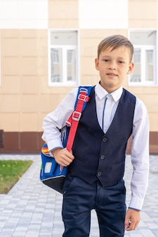 Маленький ребенок со школьной сумкой идет в школу