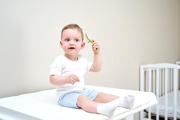 Маленький ребенок с голубыми глазами держит в руках гребешок.