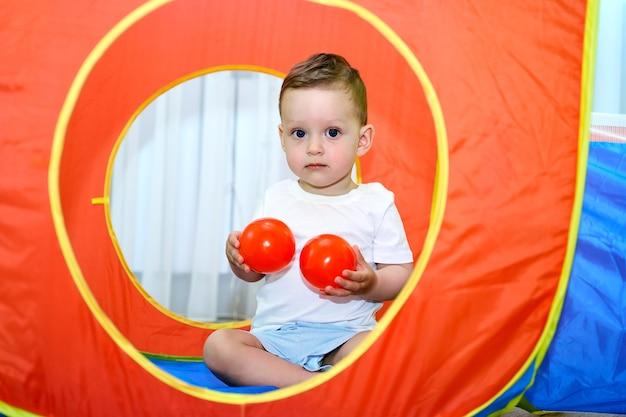В игровой комнате играет маленький ребенок с голубыми глазами.