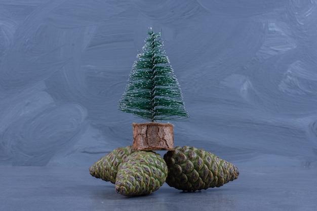 Маленькая новогодняя елка с шишками на серой поверхности