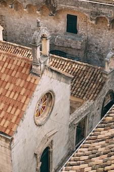 두브로브니크 크로아티아의 둥근 스테인드글라스 장미꽃과 기와 지붕이 있는 작은 교회