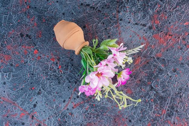大理石の背景に花の花束と小さな粘土のボウル。