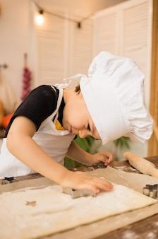 작은 요리사 소년이 부엌의 나무 테이블에서 반죽으로 진저 브레드 쿠키를 만듭니다.