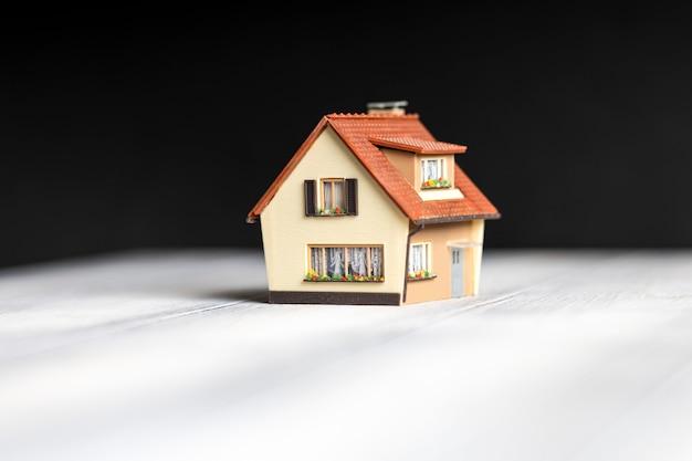 Небольшая копия дома находится на столе на черном фоне.