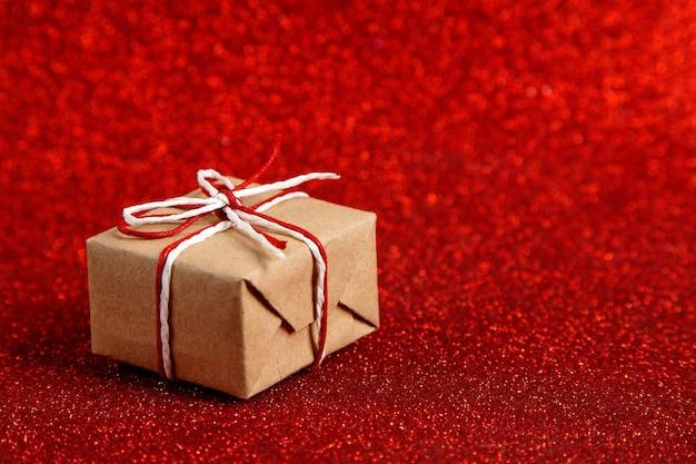 Подарок небольшой поделки на красном блестящем, пайетках сбоку. концепция ко дню святого валентина.