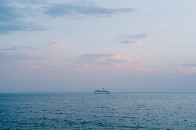 小さなクルーズ客船がオレンジ色の雲と夕日の空を背景に外洋を航行します