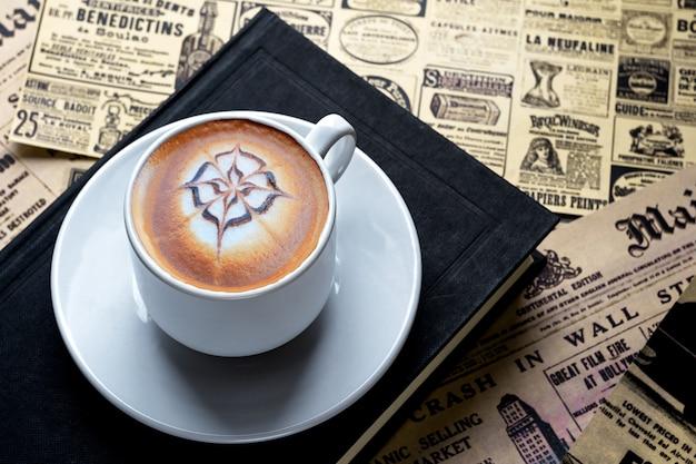古い新聞が広げられたテーブルの上の本に、受け皿にカプチーノの小さなカップが置かれています
