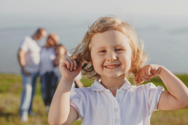 흰색의 작은 곱슬 머리 소녀는 자연에서 여름에 그녀의 부모의 배경에 대해 프레임으로보고 미소