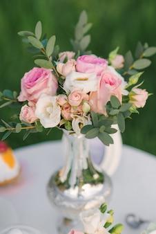 Маленький милый и нежный букет из роз и эустомы с эвкалиптовыми ветвями в серебряной вазе в декоре свадьбы или романтического ужина или обеда
