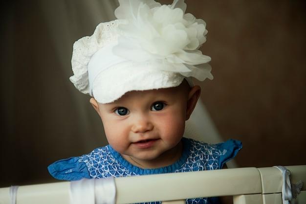 Маленькая милая очаровательная малышка в красивой шапочке смотрит прямо