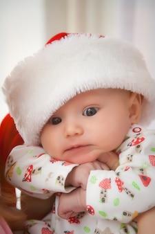 Маленькая милая очаровательная малышка в новогодней шапке смотрит прямо