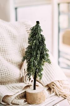 작은 장식용 녹색 나무는 창 옆의 따뜻한 니트 스웨터 옆에있는 나무 벤치에 선다.