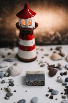 Небольшой декоративный маяк с морскими ракушками и галькой, летние каникулы и концепция отпуска