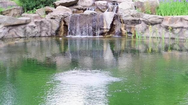 작은 장식 폭포가 연못으로 튀었습니다. 공원이나 정원에서 돌과 물을 사용한 조경. 열대우림의 자연 풍경.