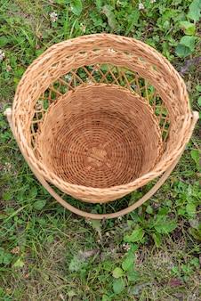 Маленькая пустая плетеная корзина стоит на траве посреди лесопарка