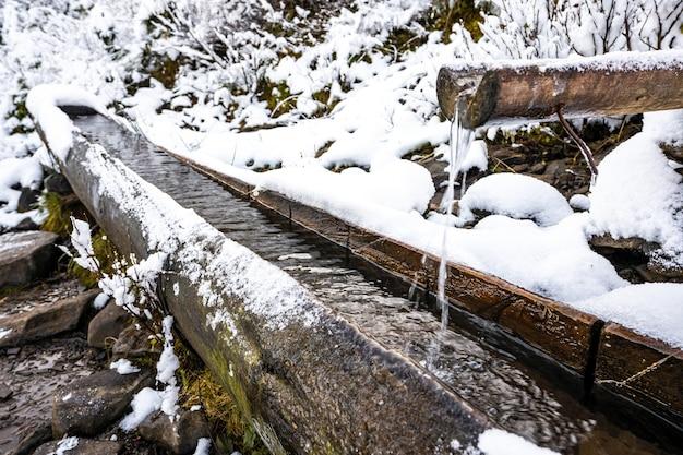Небольшой быстрый родник с чистой прохладной прозрачной водой среди сильного снега и темного леса в живописных карпатах.