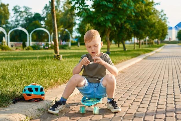 小さな5歳の男の子がスケートボードに座っていて、絆創膏で傷口を塞ぎたいと思っています